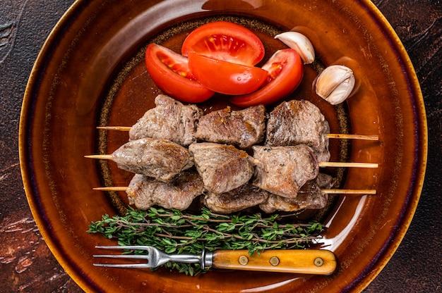 Bbq lamsvlees op houten spiesjes met groenten op een rustieke plaat