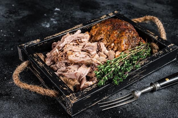 Bbq langzaam gebraden puilled varkensvlees in een houten dienblad. zwarte achtergrond. bovenaanzicht.