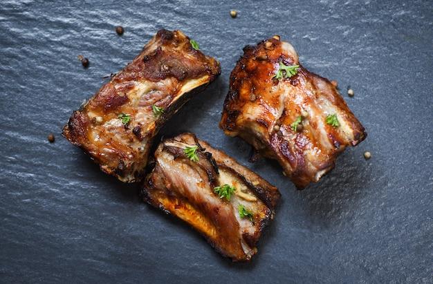 Bbq varkensribbetjes gegrild met kruiden en specerijen donkere plaat geroosterde barbecue varkensribbetjes gesneden