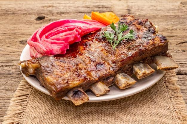 Bbq varkensribbetjes met gefermenteerde kool, gebakken wortel en verse peterselie