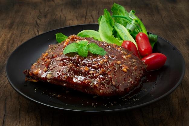Bbq varkensribbetjes met saus geserveerd met groente en tomaten