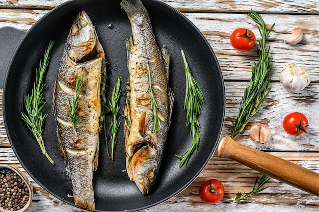 Bbq zeebaarsvis, gebakken zeebaars in een pan. witte houten achtergrond. bovenaanzicht.