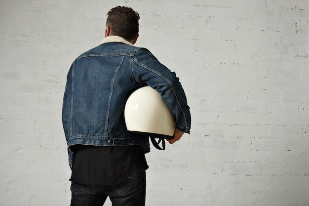 Bck uitzicht op moto biker draagt shearling denim jasje en zwart leeg henley shirt, houdt vintage beige motorhelm, geïsoleerd in het midden van witte bakstenen muur