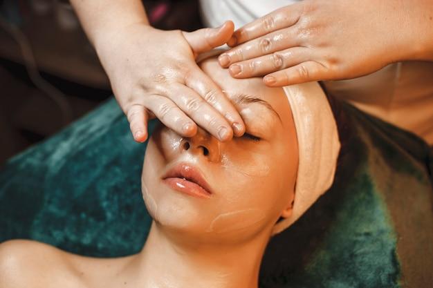 Bclose-up van de hand van de schoonheidsspecialist die gezichtsmassage doet met een vrouw in een wellnesscentrum.