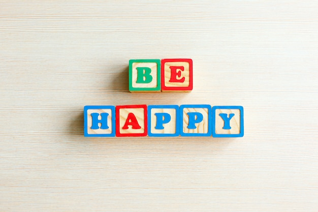 Be happy word in color wooden cube stamp