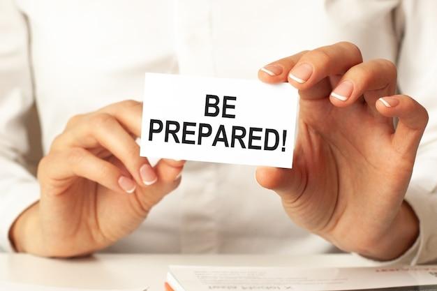 Be prepared, bericht op visitekaartje getoond door een vrouw. witte achtergrond. bedrijfsconcept voor bedrijven