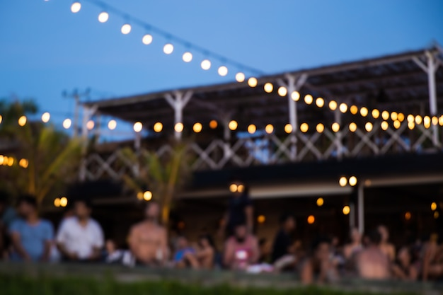 Beach party bij zonsondergang met vrienden gesloten voor zwembad met uitzicht op de oceaan. onscherpe achtergrond.