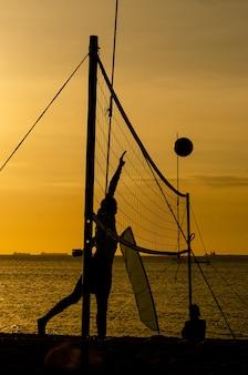Beachvolleybal silhouetten bij gele zonsondergang