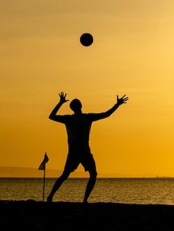 Beachvolleybal silhouetten bij zonsondergang geel
