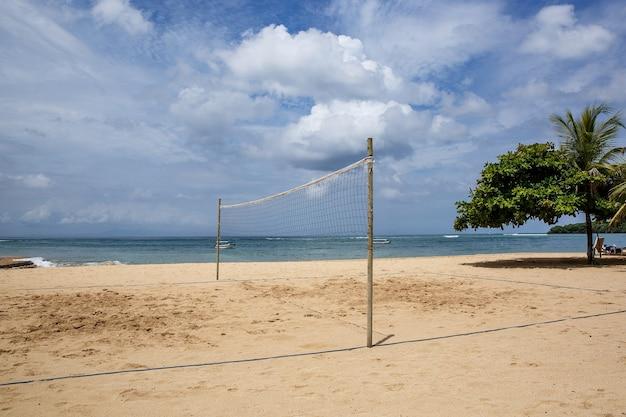 Beachvolleybalveld. zand en mesh op de oceaan.