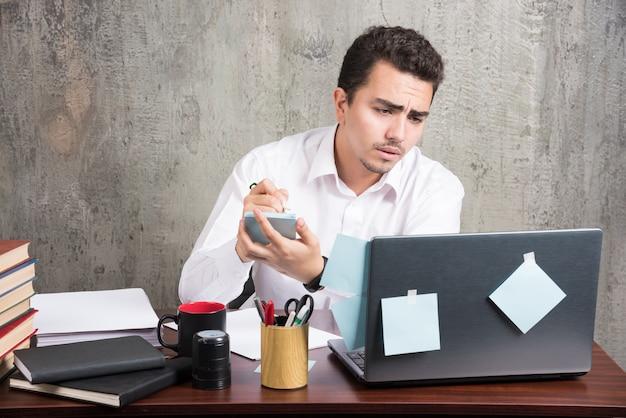 Beambte die laptop bekijkt en telefoon bij het bureau houdt.