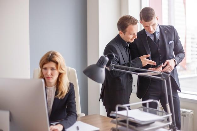 Beambten bij computer in modern bureau