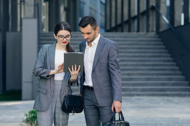 Beambten die tabletcomputer bekijken. jonge bedrijfsmensen die over een tablet bespreken.