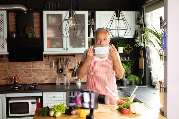 Bearded senior man groenten voorbereiden om een bord eten beperkt door covid-19 thuis met masker te maken.