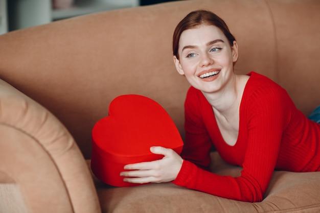 Beautifil jonge vrouw met rood haar liggend in haar bank in de woonkamer en met de geschenkdoos in de vorm van hart en glimlach. valentijnsdag of verjaardag