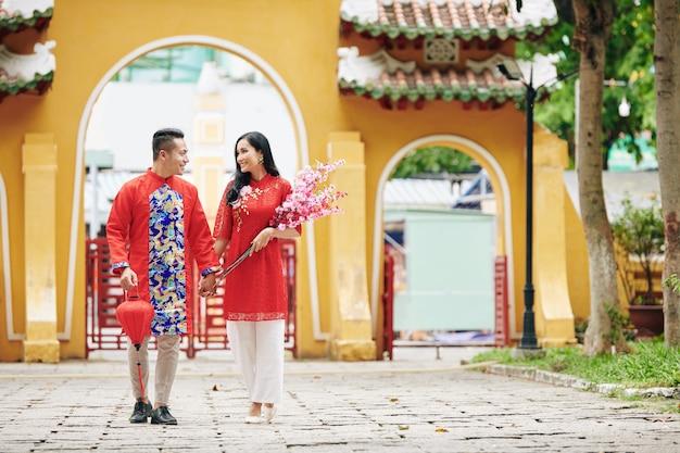 Beautifujl jong net getrouwd stel in traditionele kleding hand in hand en wandelend op straat met een bos perziktakken