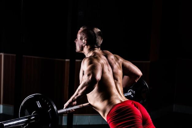 Beautiful bodybuilder is bezig met een simulator in een moderne sportschool