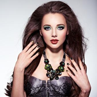 Beautiul vrouw met lange bruine haren, turquoise make-up en nagels