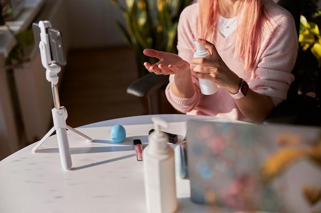 Beauty blogger fles cosmetisch product dat nieuwe video opneemt in zonnige kamer