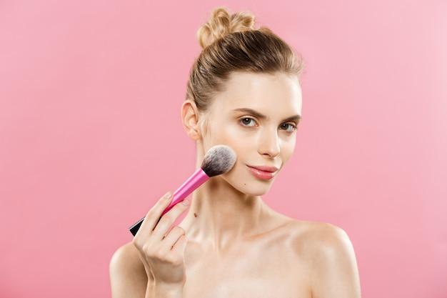 Beauty concept - close-up portret van aantrekkelijke kaukasische meisje met schoonheid natuurlijke huid geïsoleerd op een roze achtergrond met kopie ruimte.