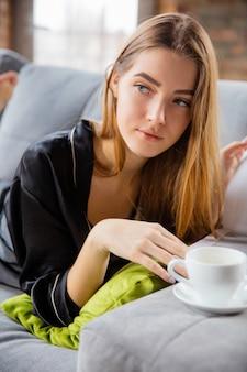 Beauty day voor jezelf. vrouw die zijden gewaad draagt die haar dagelijkse huidverzorgingsroutine thuis doet. op de bank liggen, tijdschriften lezen, koffie drinken. concept van schoonheid, zelfzorg, cosmetica, jeugd. detailopname.