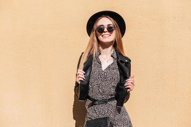 Beauty fashion hipster vrouw met witte perfecte glimlach in stijlvolle herfstlook kleding met zonnebril kijkend naar camera in de buurt van een muur op zonnige dag