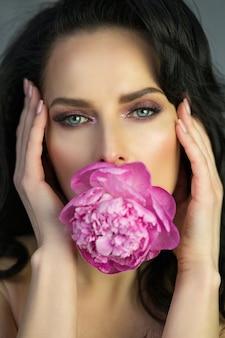 Beauty shot van aantrekkelijke brunette vrouw met roze pioenroos in mond