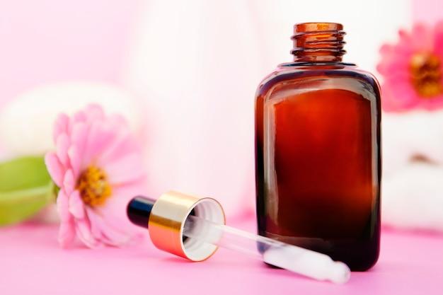 Beauty spa cosmetica, salon therapie. glazen flesje op roze.