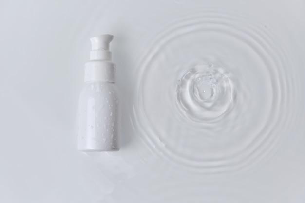 Beauty spa medische huidverzorging en cosmetica. lotion dispenser fles mock up crème verpakkingsproduct op wit water achtergrond met druppels, zomer vers concept.