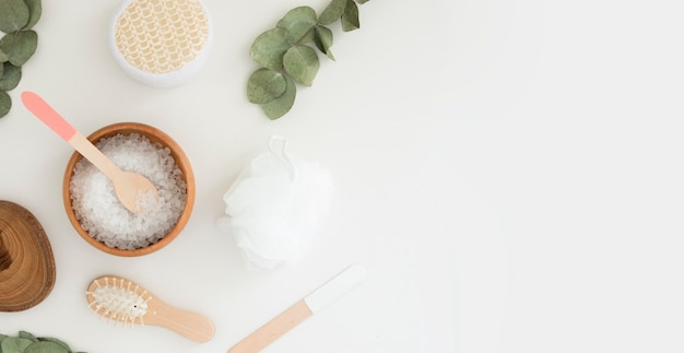Beauty spa plat lag met zout, eucalyptus en houten accessoires op witte achtergrond