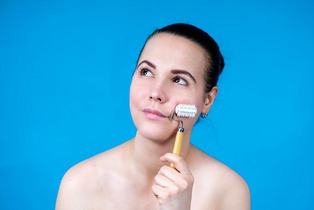Beauty spa portret van mooie gelukkige vrouw die masseert met gezichtsroller op haar schone schone?