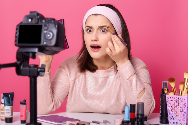 Beautyblogger neemt video op over nieuwe cosmetica. geschokte vrouw toont geen kwalitatieve oogschaduw in haar internetvlog. donkerharige vrouw met wijd open ogen en mond houdt niet van penseel in haar hand.