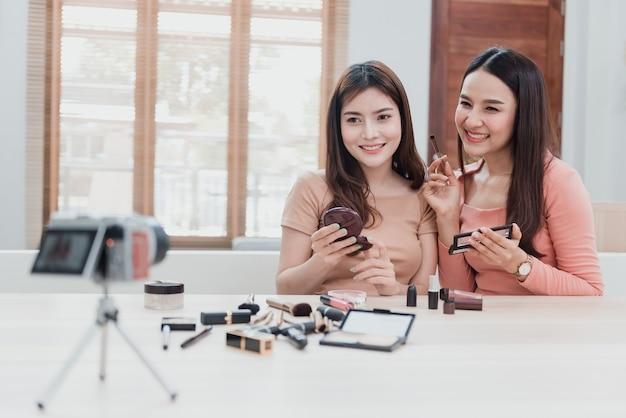 Beautybloggers, twee mooie aziatische vrouwen proberen cosmetica te begrijpen en te verkopen