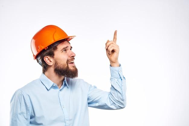 Bebaarde aannemer met oranje helm poseren tegen de witte muur
