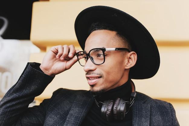 Bebaarde afrikaanse man met kort kapsel zijn bril aan te raken. close-up buitenfoto van zwarte jongen in hoed en muziekhoofdtelefoons.