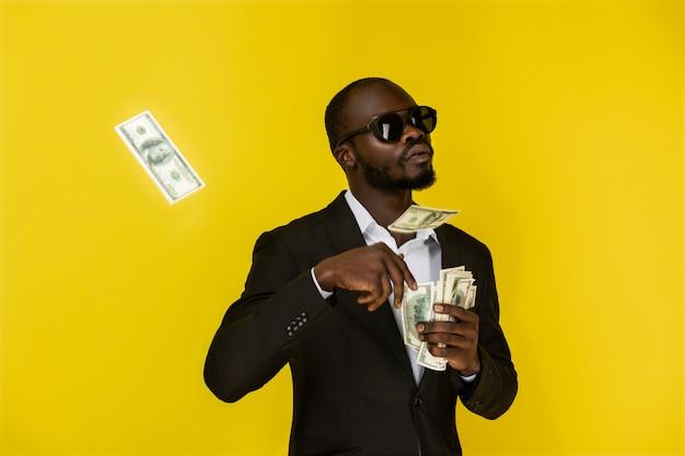 Bebaarde afro-amerikaanse man gooit dollars uit de ene hand, draagt een zonnebril en een zwart pak