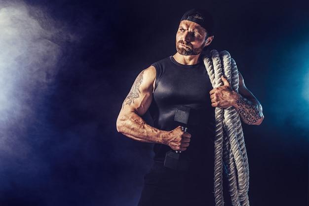 Bebaarde atletisch uitziende bodybulder die slagtouw en barbbell op donkere muur met rook houdt. kracht en motivatie.