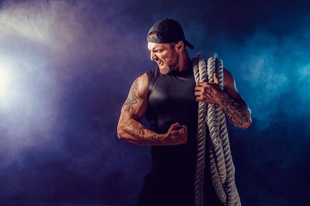 Bebaarde atletisch uitziende bodybulder die slagtouw houdt op donkere muur met rook. kracht en motivatie.