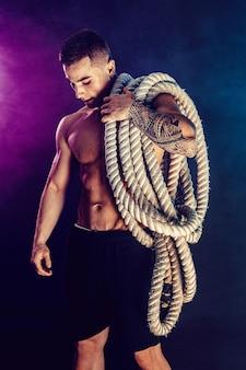 Bebaarde atletisch uitziende bodybulder die slagtouw op donker met rook houdt. kracht en motivatie.