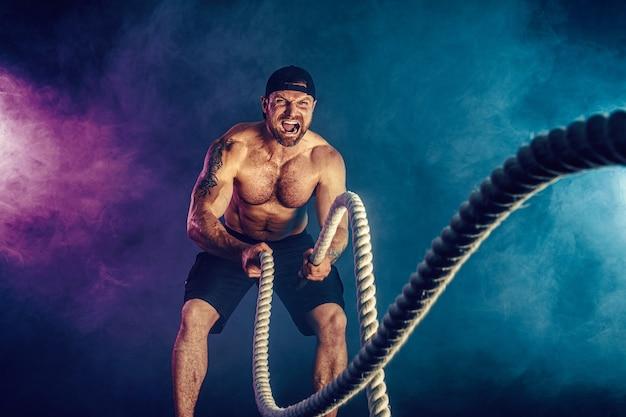 Bebaarde atletisch uitziende bodybulder trainen met gevechtstouw op donker met rook. kracht en motivatie.