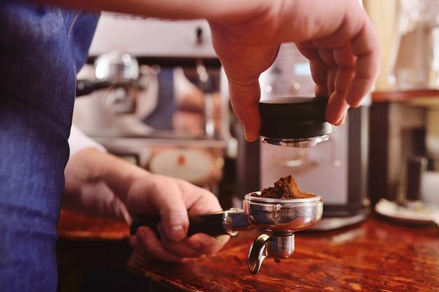 Bebaarde barista die koffie maakt