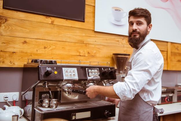Bebaarde barista maakt koffie voor een klant.