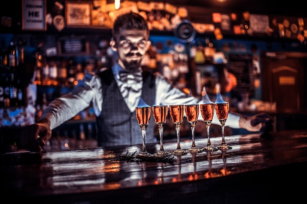 Bebaarde barman demonstreert zijn vaardigheden over de toonbank in cocktailbars