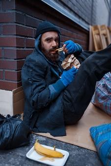 Bebaarde bedelaar eet hamburger op straat in de stad