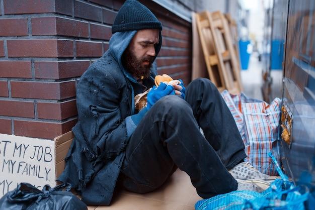 Bebaarde bedelaar eet hamburger op straat in de stad.