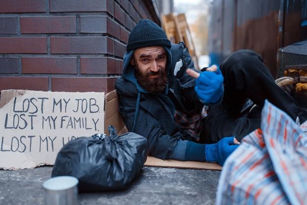 Bebaarde bedelaar slapen op straat in de stad.
