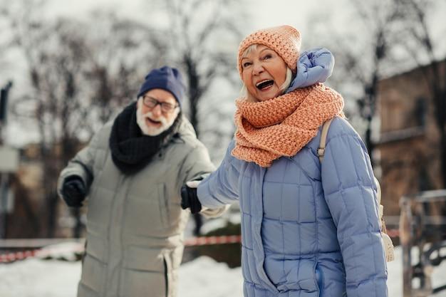 Bebaarde bejaarde man weigert te gaan terwijl zijn energieke vrouw glimlacht en zijn hand trekt. warme winterkleren op het bejaarde echtpaar