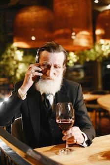 Bebaarde bejaarde zakenman. man in een restaurant. senior in zwart pak.