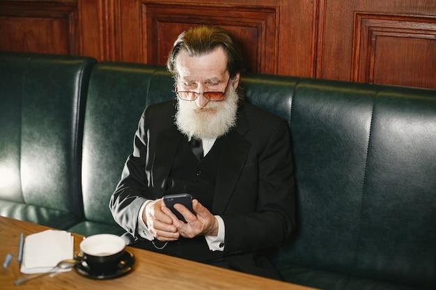 Bebaarde bejaarde zakenman. man met koffie. senior in zwart pak.