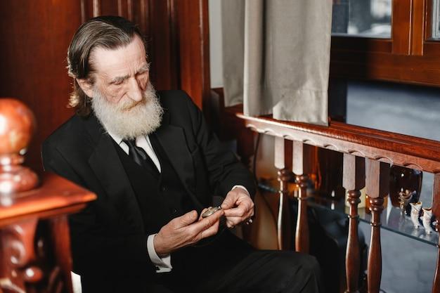 Bebaarde bejaarde zakenman. man met oud horloge. senior in zwart pak.